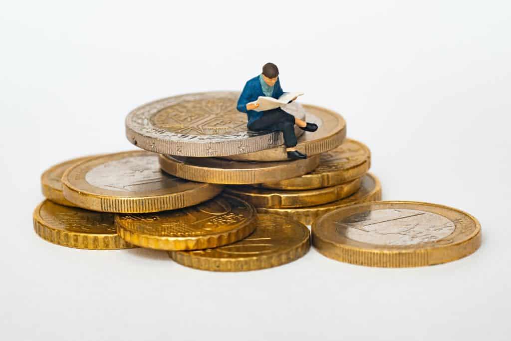 Eine winzige männliche Figur, die eine Zeitung liest und auf einem Haufen Münzen sitzt.